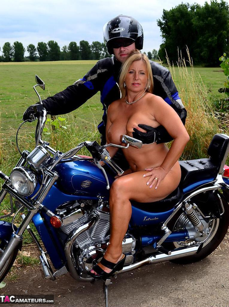 Thick biker momma with red lips gets naked on a motorcycle in a garage