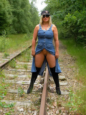 On the tracks During my walk around I found these old tracks. I decided to take some photos for You.. Cougar, milf, big tits, flashing, exhibitionist, european, boots, striptease